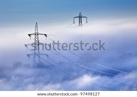 Electrical power lines and pylons emerging from the mist - stock photo