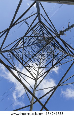 Electrical tower closeup against blue sky - stock photo
