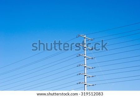 Electrical tower with multiple levels of parallel power lines and insulators, on clear blue sky background and copy space at top. - stock photo