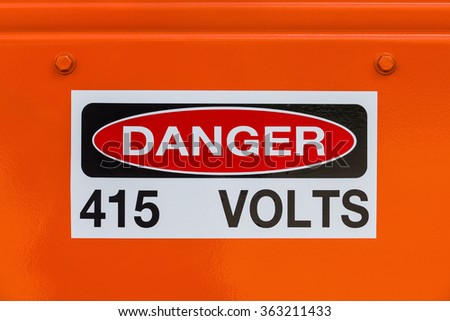 Electrical voltage (415 volts) existing danger sign on orange surface - stock photo