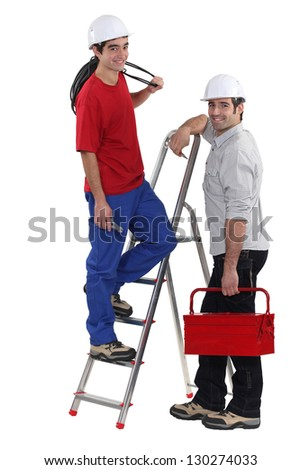 Electrician and young apprentice - stock photo