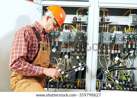 electrician at wiring work - stock photo