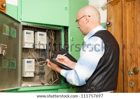 Electrician  at work inspecting cabling connection of high voltage power electric line in distribution fuseboard - stock photo