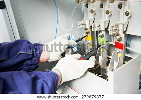 electrician builder checking voltage in electrical fuse switch distribution board - stock photo