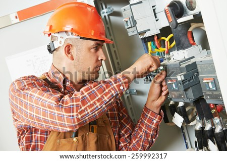 electrician builder engineer screwing equipment in fuse box - stock photo