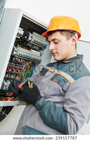 electrician builder engineer worker working with cable in fuse switch box - stock photo
