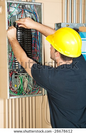 Electrician changing a breaker in a large industrial breaker panel. - stock photo