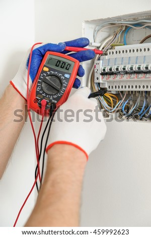 Electrician check voltage in electrical fuse box with a multimeter. - stock photo