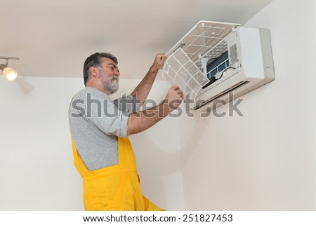 Electrician cleaning filter of air condition device in a room - stock photo
