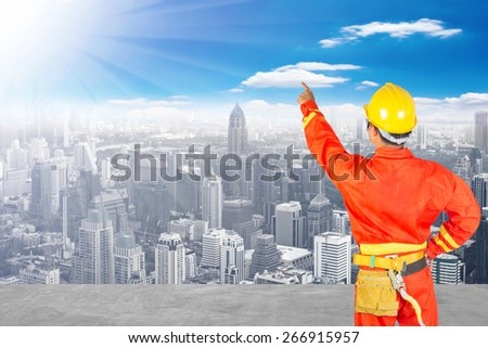 Electrician climbing ware and pointing something at high building construction site against blue sky with in concept ecology and real estate - stock photo