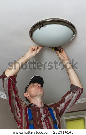 Electrician completes the installation of ceiling lamps. - stock photo