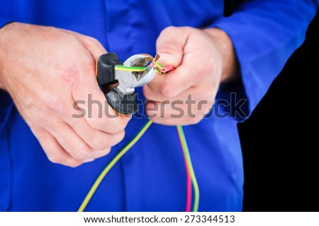Electrician cutting wire with pliers against black - stock photo
