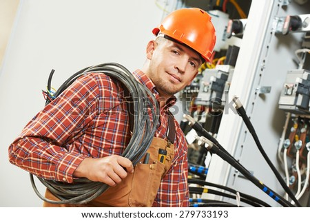 electrician engineer worker with cable in front of fuseboard equipment - stock photo
