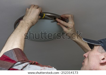 Electrician fastens glass ceiling lamp fixture. - stock photo