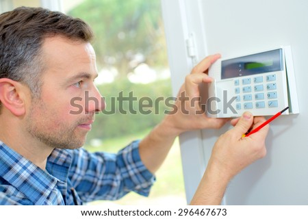 Electrician fitting an intrusion alarm - stock photo