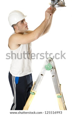 electrician fixing a lamp on a ladder - stock photo