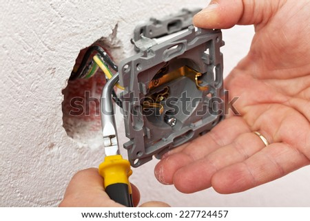 Electrician hand mounting a wall fixture - fitting the wires with pliers - stock photo