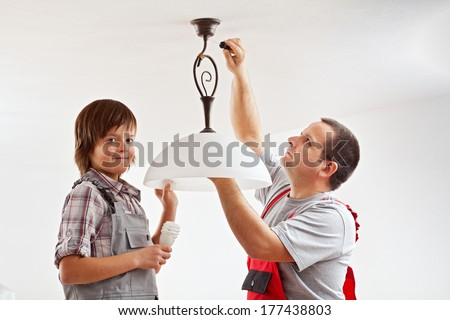 Electrician hands installing electrical wall sockets - closeup, focus on the fixture - stock photo