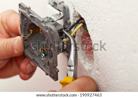 Electrician hands installing wires into electrical outlet - closeup - stock photo