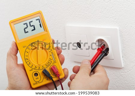 Electrician hands with multimeter - measuring voltage in electrical wall fixture - stock photo