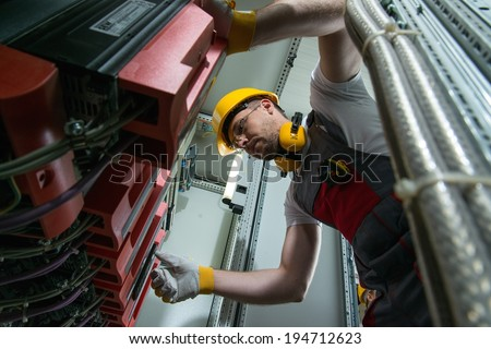 Electrician in a safety hat and headphones on a factory - stock photo