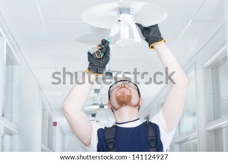 Electrician in Coverall Repairing Broken Light - stock photo