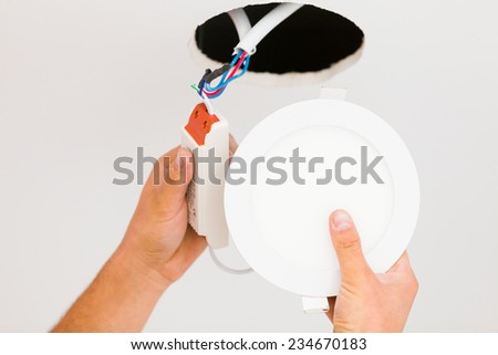 Electrician installing light on a white wall. - stock photo