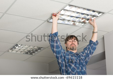Electrician installs lighting to the ceiling in the office. - stock photo