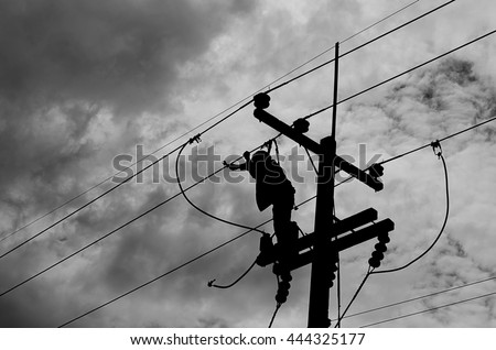 Electrician lineman repairman worker at climbing work on electric post power pole.At the time of the dark clouds cream - stock photo