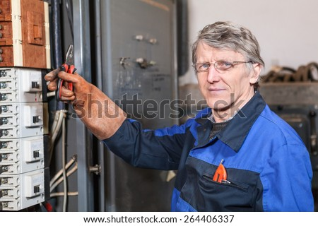 Electrician maintain worker holding pliers in hand wearing rubber glove - stock photo
