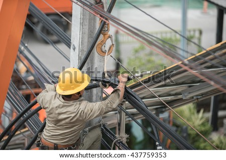 Electrician Man on electric poles. Electrical repairs are made to restore them to normal - stock photo
