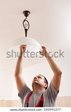Electrician man screwing a new lightbulb into ceiling lamp - closeup - stock photo