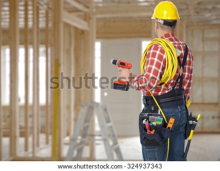 Electrician man with drill and wire cable over construction background. - stock photo