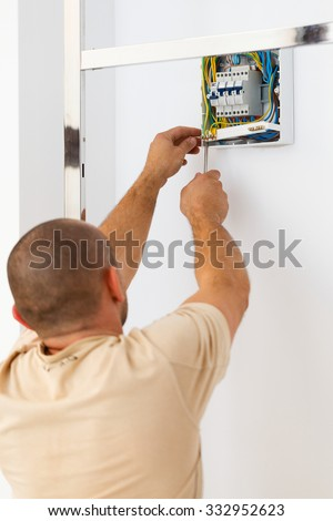 Electrician man working fixing electric fuse with tools. - stock photo