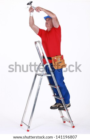 Electrician on a ladder - stock photo
