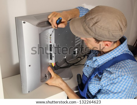 Electrician repairing a TV - stock photo