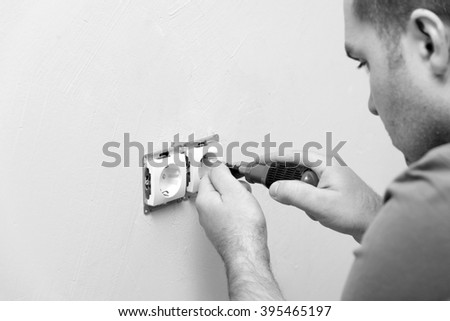 electrician repairing electrical socket on white wall