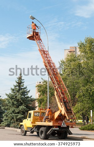 electrician repairing street light - stock photo