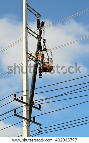 electrician repairing wire on electric power pole - stock photo