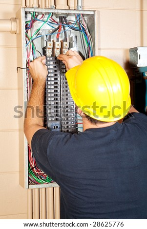 Electrician replacing a bad circuit breaker in a large industrial panel. - stock photo