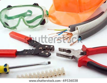 Electrician's tools. Hardhat, pliers, cables, cutter, screwdriver, etc. - stock photo