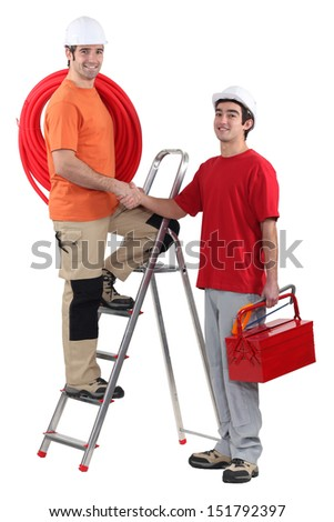 Electrician shaking other worker's hand - stock photo