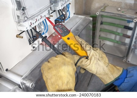 Electrician testing industrial machine - stock photo