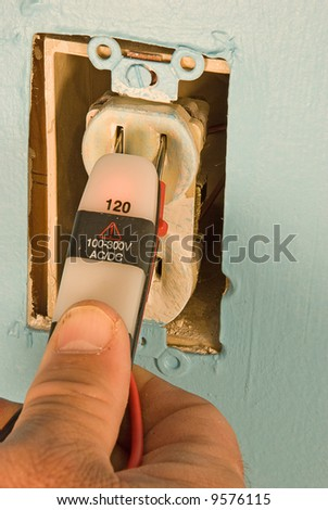 Electrician testing voltage in a home electrical outlet - stock photo