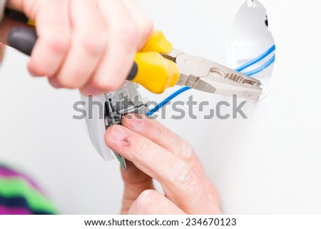 Electrician using tools for installing light. - stock photo
