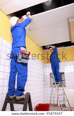 Electrician wiring a large tiled room - stock photo
