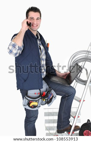Electrician with a cellphone and laptop - stock photo