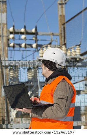 Electrician with computer near the electricity substation - stock photo