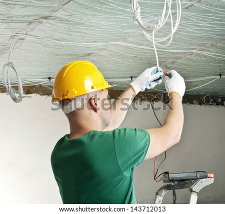 electrician with multimeter checking voltage - stock photo