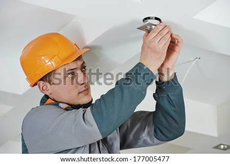 electrician worker in uniform installing or replacing spot light lamp into ceiling - stock photo